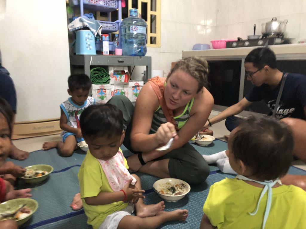 Feeding dinner to children at nightcare in Cambodia